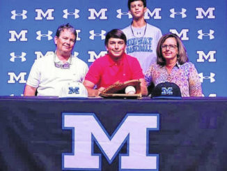 Cal Tyndall is joined by his parents Mark and Amy and brother Hunter during a recent signing event held at Midway.