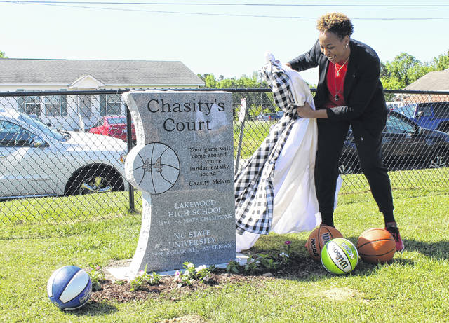 <p>Chasity Melvin smiles while pulling the tarp off a monument dedicated to her. The revamped court in Roseboro was named in her honor last year.</p>