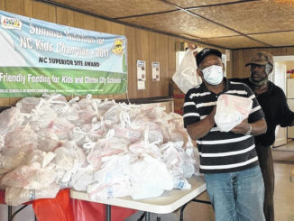 Charles Strickland, left, distributes meals with the help of volunteers.