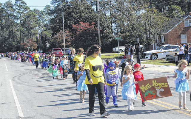 Young students from Salemburg Elementary School participate in a fall parade while wearing costumes.