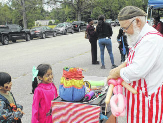 Carlton Smith enjoys making balloons for Violeta and Sylvester Covarrubias during a past Community Day in Garland. The event has been canceled this year.                                  File Photo | Sampson Independent