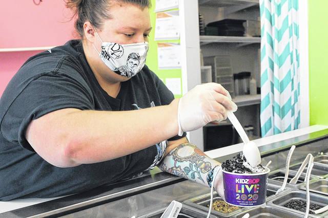 <p>Harlee James tops some yogurt with Oreo topping.</p>