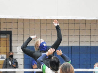 Makenzi Hudson eyes the ball as she takes a swing to send it back over the net.