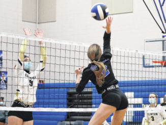 Midway's Taylor Williams returns the ball toward a block-attempting Abigail Batchelor