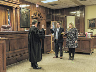 Robert Gilmore takes an oath to become the District 4, Seat 5 judge while his wife Ashley holds the Bible. Henry L. Stevens IV, left, administered the oath.