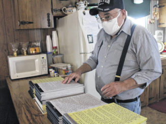 Joseph McNeill looks at the stack of tablets that make up his handwritten bible.