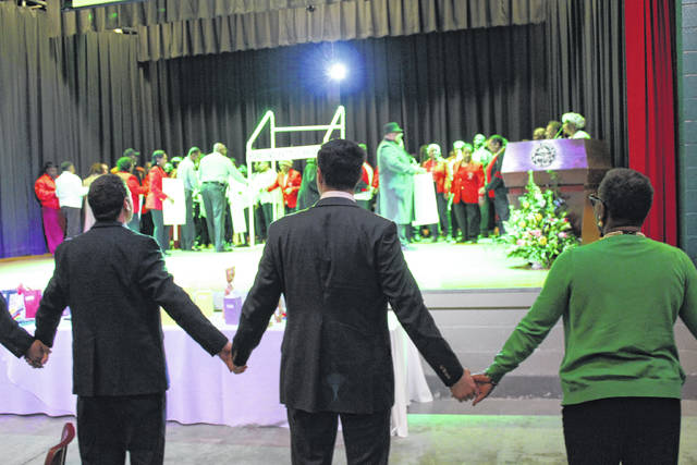 <p>Audience members hold hands together in unity during 2020's event.</p>