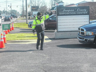 A Clinton Police officer directs traffic in the waiting area of the drive-through mass vaccination clinic.                                  Chase Jordan|Sampson Independent