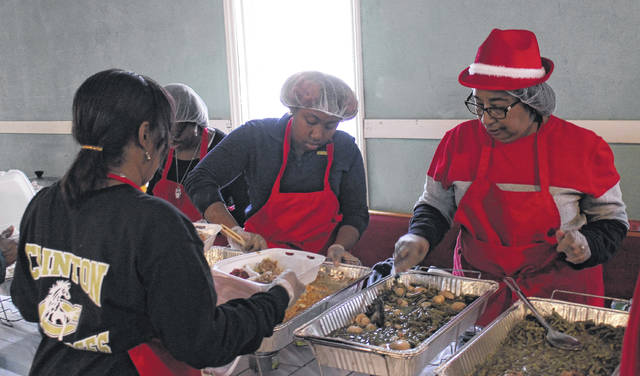 Volunteers from the Friendly Trio Community Development Center prepare meals for a holiday celebration in 2019.