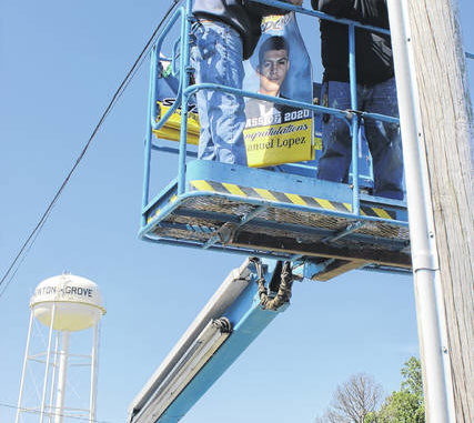 In downtown Newton Grove, parent William Phipps and Hobbton High Principal Michael Warren prepare to attach a banner to a pole. The project was a way to honor students from the Hobbton High School Class of 2020.                                  File photo|Sampson Independent