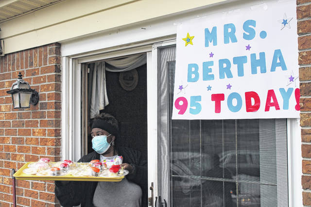 <p>Patricia Cooper delivers cupcakes to birthday parade participants.</p>                                  <p>Chase Jordan Sampson Independent</p>