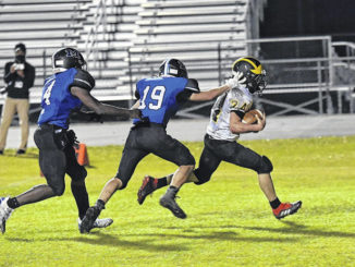 Bobby Dial gets in for a touchdown early in the game, slipping past Midway's Jonathan Cooper and Isaiah McClendon.