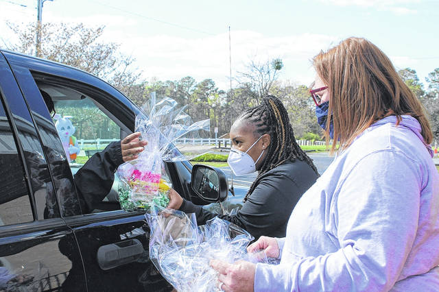 <p>Recreation Program Manager Alyssa Bradshaw and Vonnie McNeil hand out Easter baskets.</p>