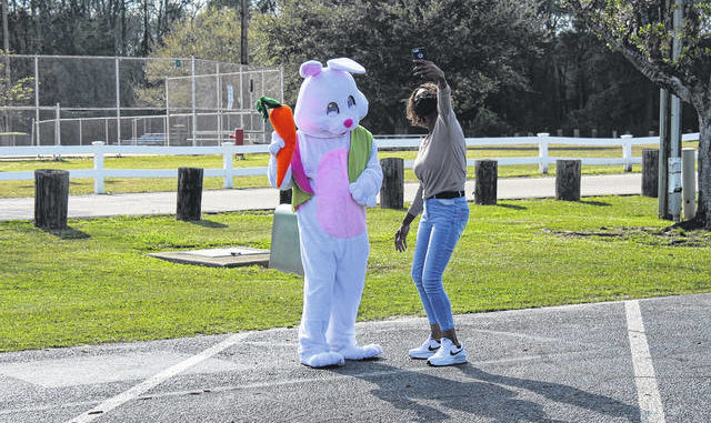 A woman stops to dance with the Easter Bunny at the Easter Eggspress event.