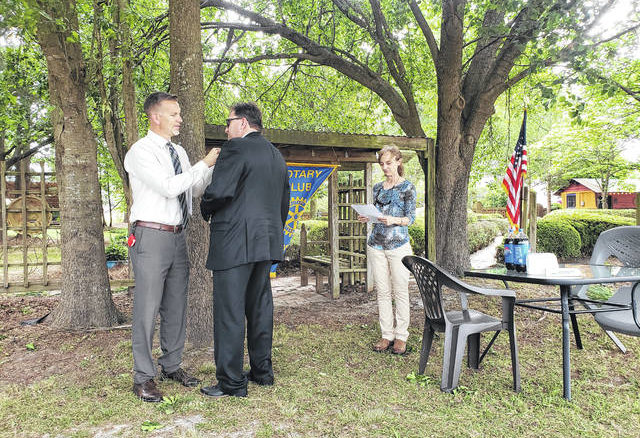 Sampson Rotary member Dr. Wesley Johnson, left, affixes a new member pin on Dr. David Goodin during an installation service at Twiddle Dee Farm Monday. Club president Eileen Coite gave the charge, urging Goodin, new Sampson County Schools superintendent, to tout Rotary in the community and reach out a hand to bring new members to the club.