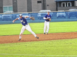 Caden Wilson fields a routine infield hit and looks toward first base to make the play.