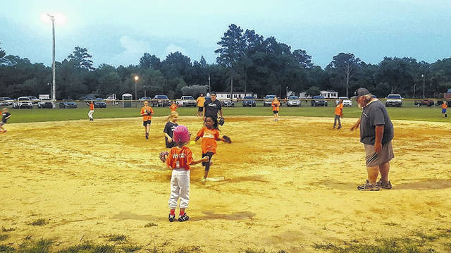 Children compete as part of the Garland Volunteer Softball League.