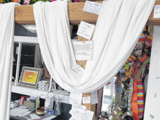 Small papers are pinned to the cross at Atrium Florist & Gifts in Clinton as an opportunity to pray and be in prayer for others in need.                                  Emily M. Williams | Sampson Independent