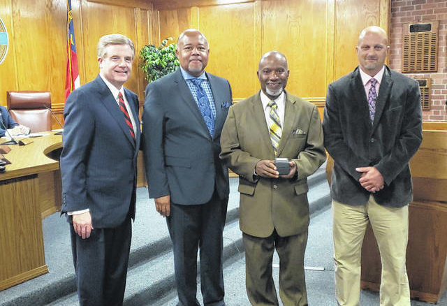 Retiree Lionel Raynor, center right, poses with, from left, Clinton Mayor Lew Starling, Councilman Marcus Becton and Public Works Director Chris Medlin.