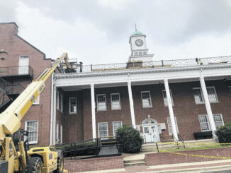 Crews work to rehaul the Sampson County Courthouse roof, the final bid for which was approved earlier this month.                                  Chris Berendt Sampson Independent