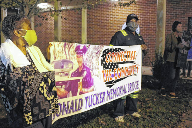 Glenda and Billy Tucker hold a banner outside of Clinton City Hall before a City Council meeting last year in a call for the Faircloth Freeway bridge to be named after their son, Donald Ray Tucker.                                  File photo|Sampson Independent