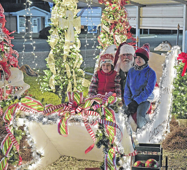 <p>Two youngsters discuss their Christmas requests with Santa Claus during Circle of Lights in Newton Grove last year.</p>